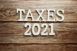 Taxes 2021 alphabet letter on wooden background